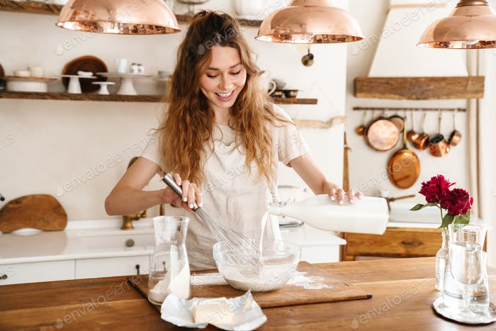 Attractive young cheerful girl baking at the kitchen
