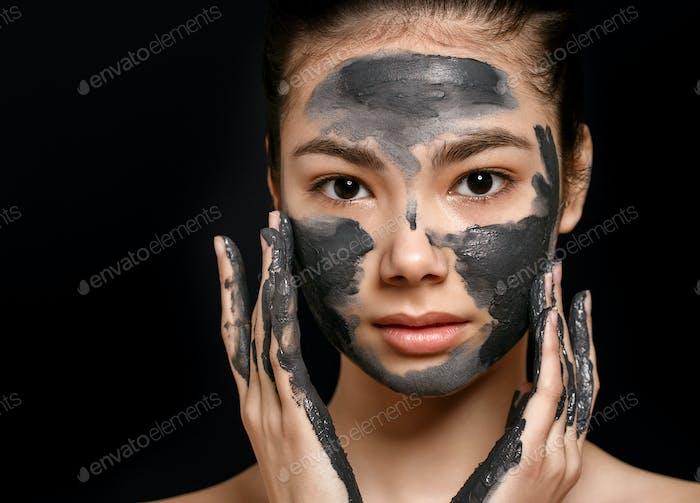 Mujer con máscara de raspado cosmético en la cara.