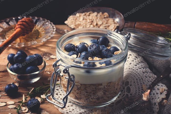 Muesli with yogurt and blue berries in glass jar.