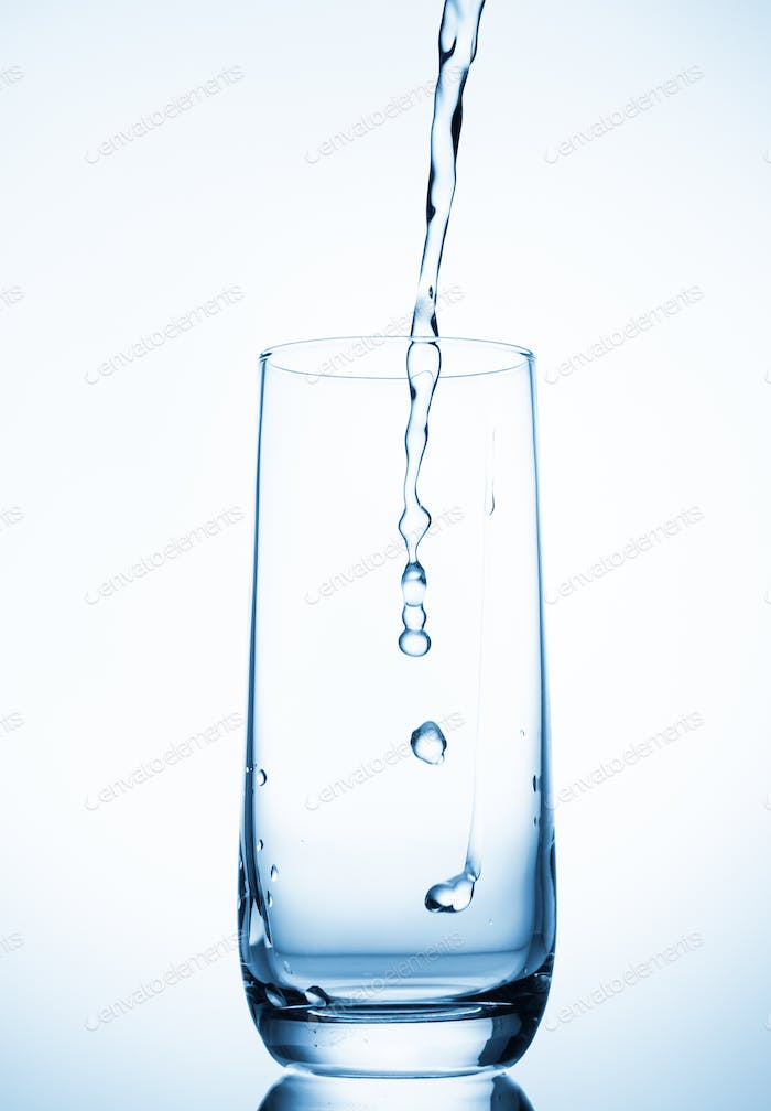 water pouring into glass over blue background.
