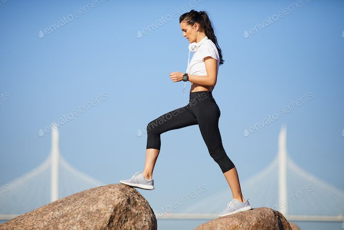 Sporty woman stepping on stones