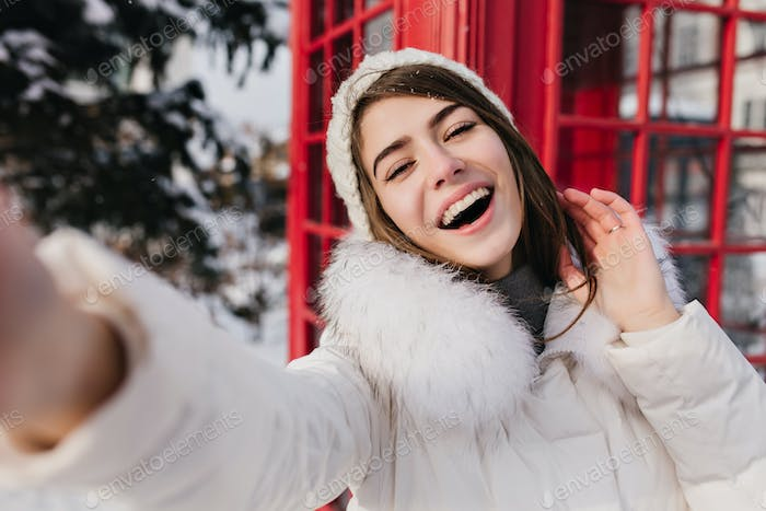 Outdoor portrait of cute woman with happy smile making selfie in London during winter vacation. Ador