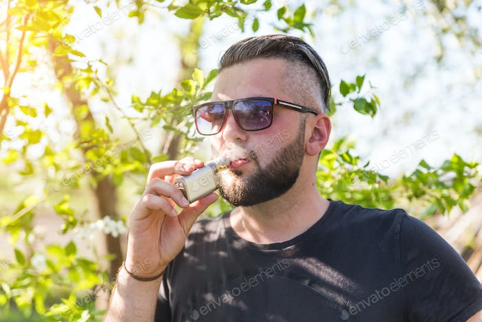 Portrait of young guy with beard vaping an electronic cigarette with puffs of steam at sunset
