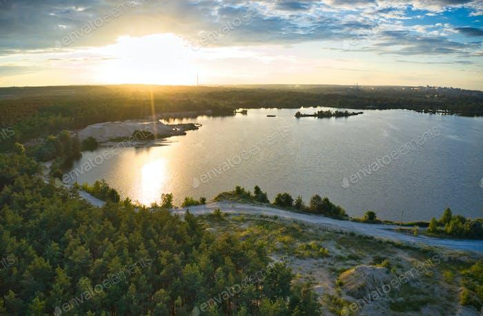 Lago cerca del bosque y la ciudad en el fondo