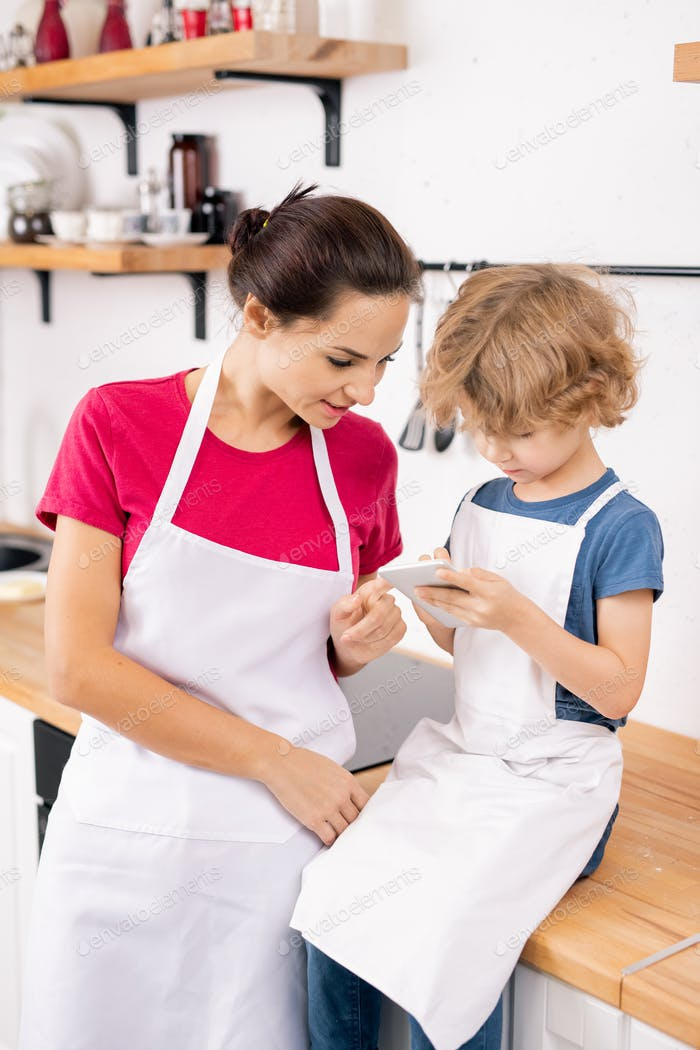 Cute little boy and his mother in aprons discussing ingredients of recipe