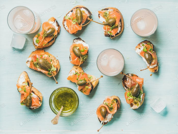 Crostini with smoked salmon and pink grapefruit cocktails, flat-lay
