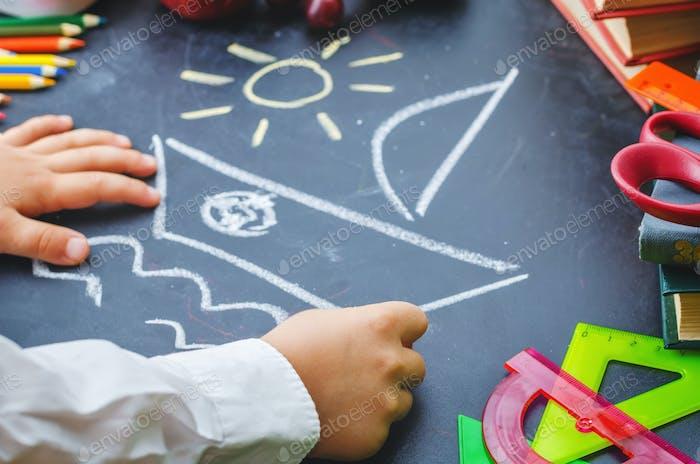 Kinderhände schreiben auf einer Tafel. Schulkonzept