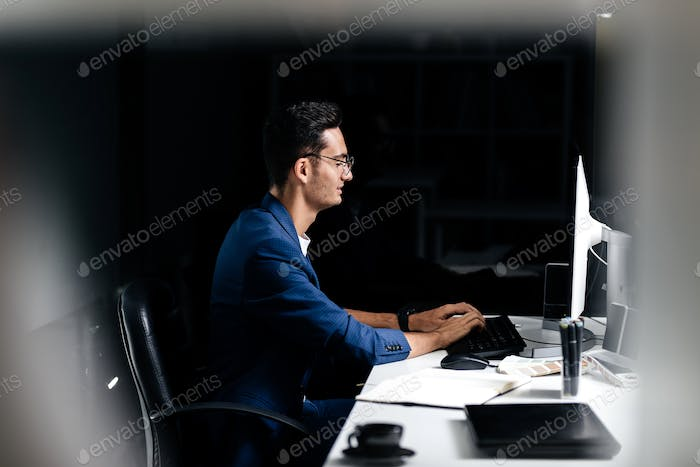 The architect in glasses dressed in a blue jacket sits at the desk and works on the computer in the