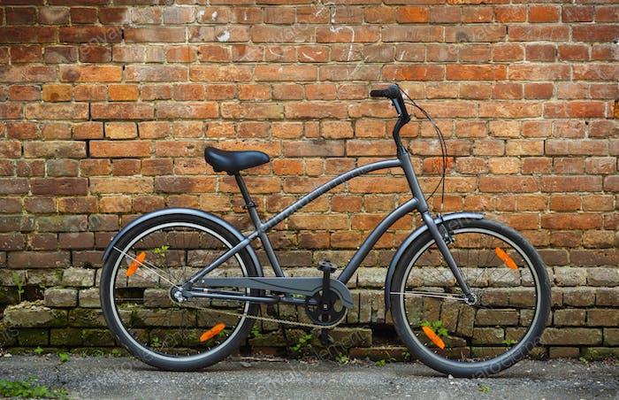 Black retro vintage bicycle with brick wall