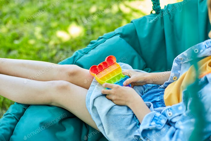 A little girl the on hanging chair outdoors play pop it, kid hands playing with colorful pop It