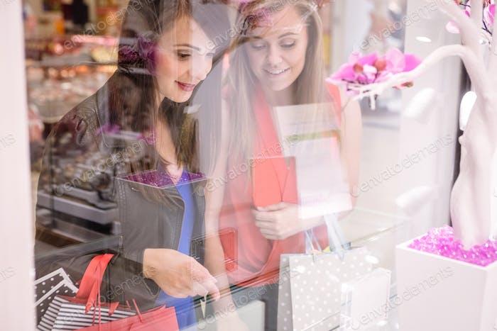 Zwei schöne Frauen Fenster Shopping in Mall