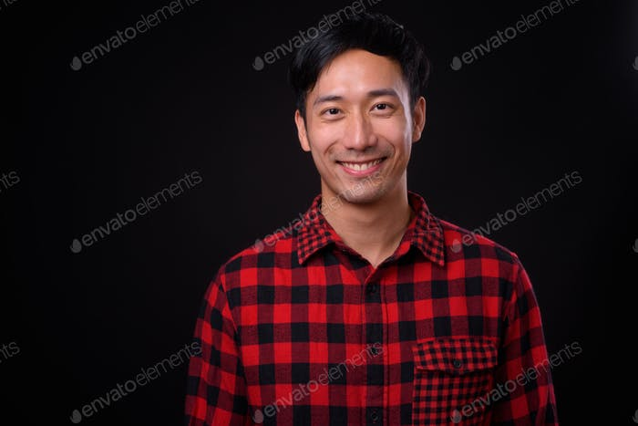 Young handsome Asian man against black background