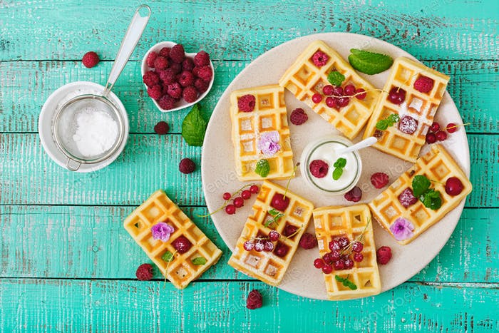Belgium waffles with raspberries and yogurt on plate. Flat lay. Top view