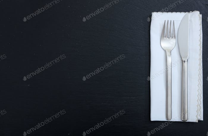 Cutlery and napkin on black background