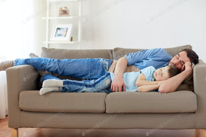 happy father and son sleeping on sofa at home