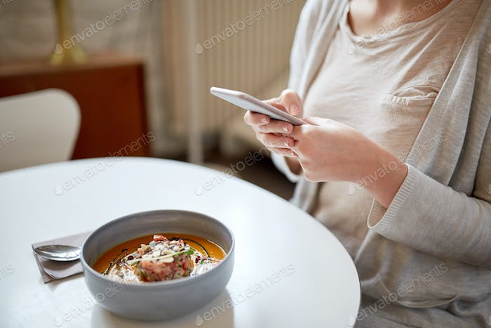 woman with smartphone and pumpkin soup at cafe