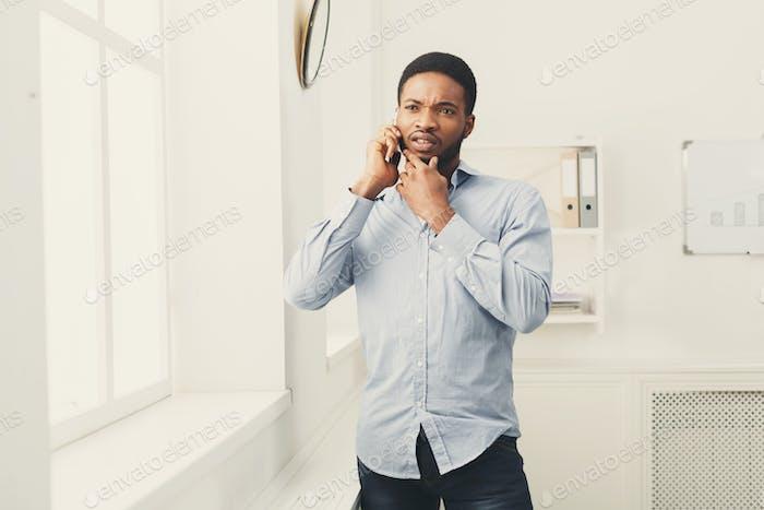 Бизнесмен телефон разговаривает по телефону возле окна