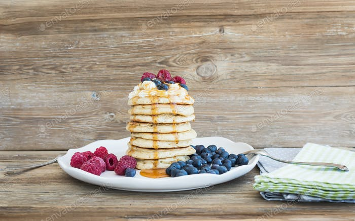 Pancakes with creamy cheese topping, garden berries and maple sy