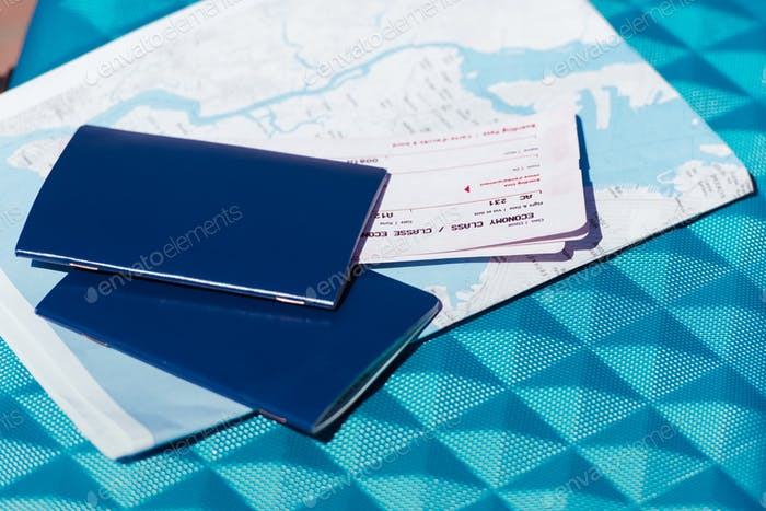 close up of map, two passports and tickets lying on blue baggage