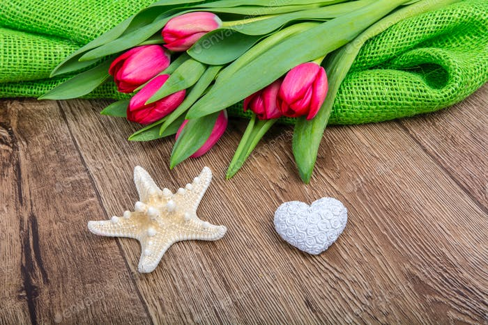 Starfish, heart and tulips on a wooden table