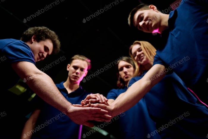 Team of five successful young e-sports clubbers making pile of hands