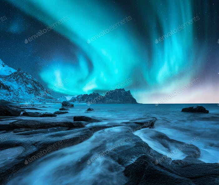 Northern lights over snowy mountain and sandy beach with stones