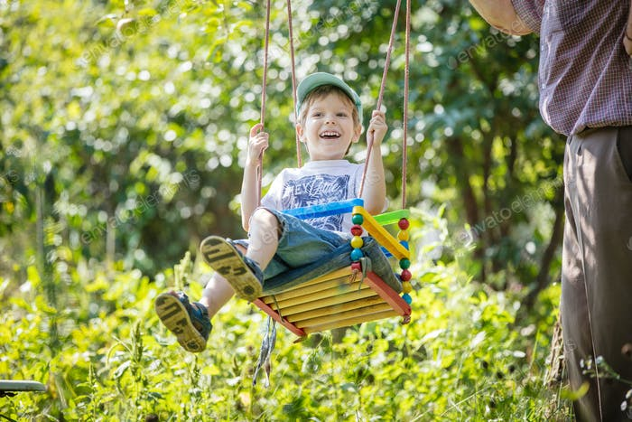 Senior man pushing laughing grandson on swing