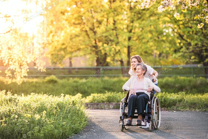 Elderly grandmother in wheelchair with granddaughter in spring nature.