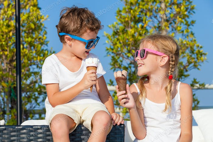 Two happy children eating ice cream near swimming pool at the da