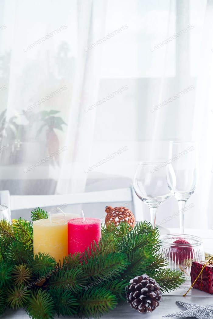 Christmas wreath with colorful big candles on a table with a Christmas table setting