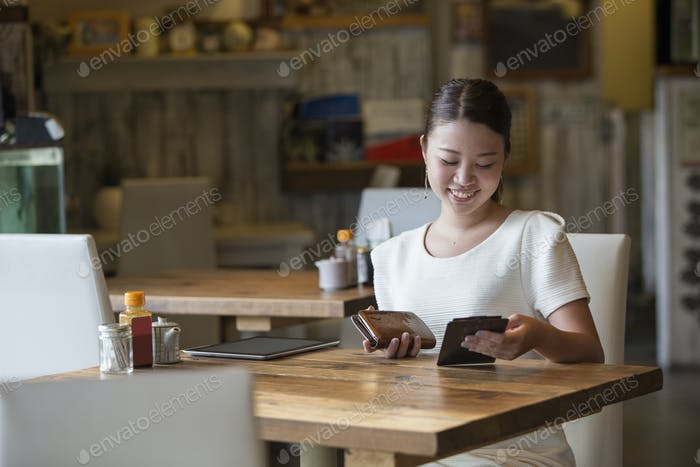 Frau sitzt an einem Tisch in einem Café, hält die Rechnung und ihre Geldbörse, lächelnd.