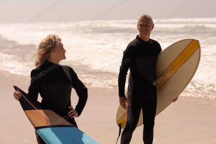 Vista frontal de pareja senior con tabla de surf de pie en la Playa y mirando uno al otro en un Día soleado