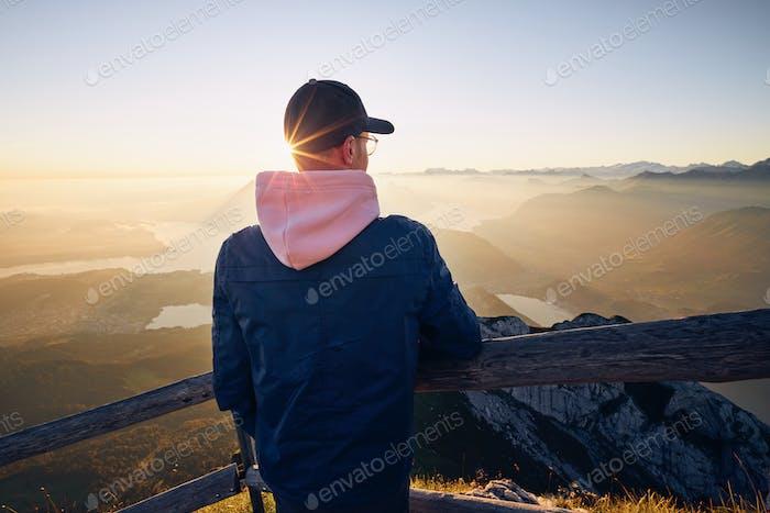 Hiker looking at mountain range at sunrise