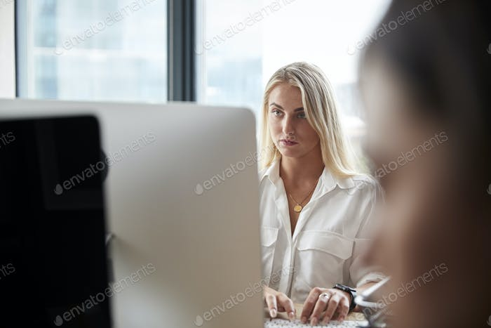 Young white blonde woman working at a computer in a busy creative office, close up
