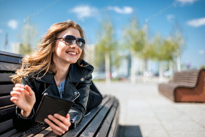 Woman sitting on bench among urban space and reading ebook using digital reader