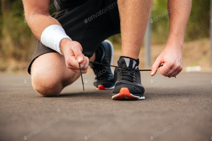 Handsome young sportsman tying shoelaces on his sneakers