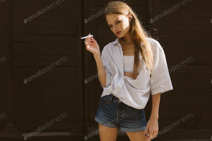 Young beautiful serious woman in white shirt and denim shorts ho