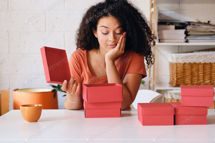Young attractive lady sitting at the table with cup of coffee thoughtfully opening little red box