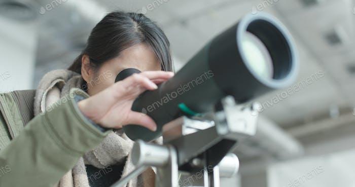 Frau schaut durch Teleskop, um den Vogel zu beobachten