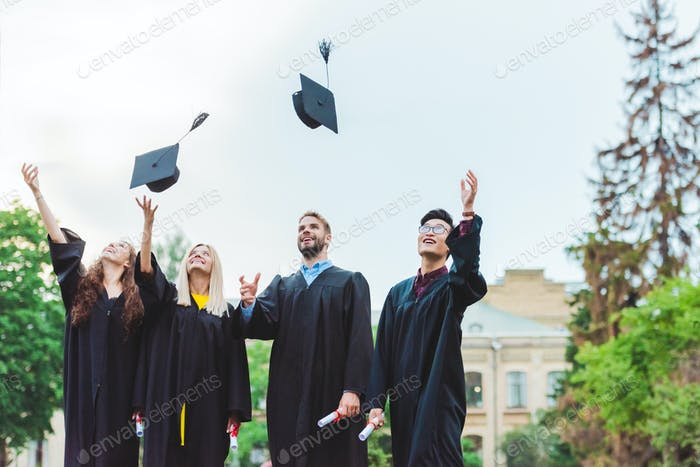 portrait of happy multicultural graduates with diplomas throwing caps up in park