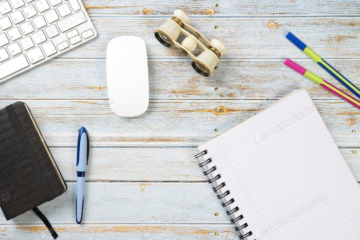 Office desktop with binoculars, keyboard, mouse, coloured pens, diary and a white notebook