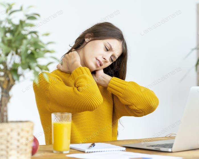 Woman massaging neck pain from working at computer for long time