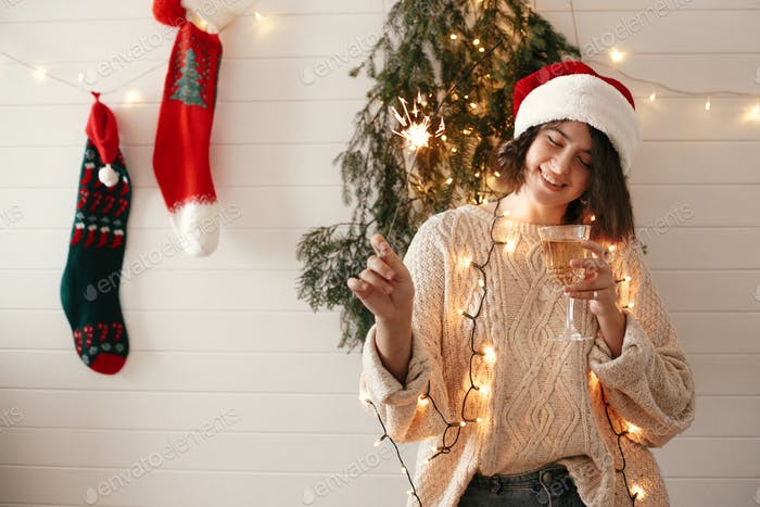 Stylish happy girl in santa hat holding sparkler and champagne glass