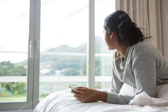 Woman looking away while holding digital tablet on bed