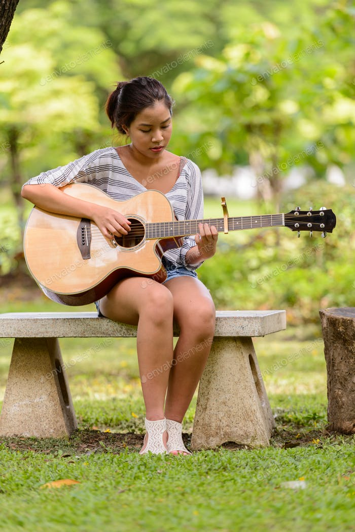 Full body shot of young Asian woman playing guitar at the park