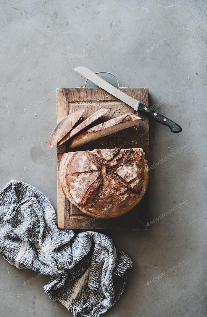 Freshly baked sourdough wholegrain bread on rustic wooden board