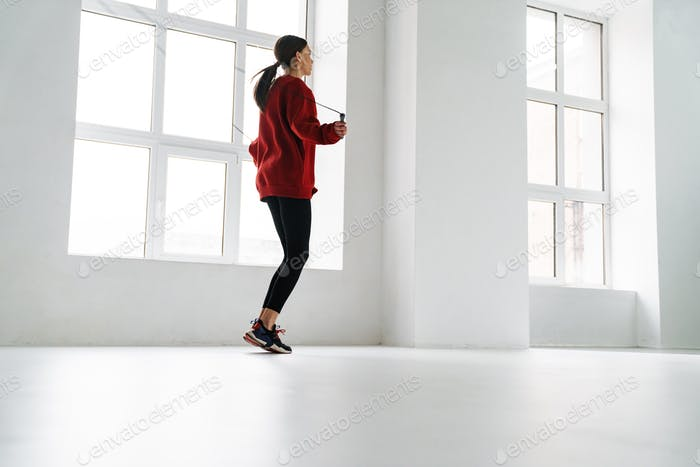 Athletic young sportswoman working out with jumping rope