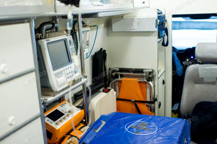 Stretcher by first aid medical equipment and other stuff inside ambulance car