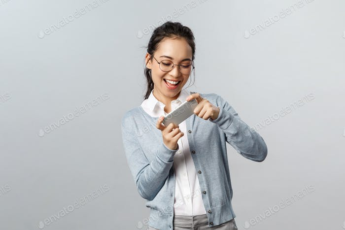 Technology, online and mobile lifestyle concept. Enthusiastic, happy smiling asian woman holding