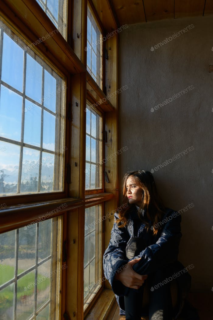 Young beautiful Asian woman sitting in front of closed wooden window with sunlight streaming in